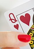Hand holding a queen of hearts card